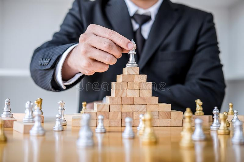 Wooden game of strategy, Hands of confident businessman playing chess game to development analysis new strategy plan, leader and. Teamwork concept for win and stock photo