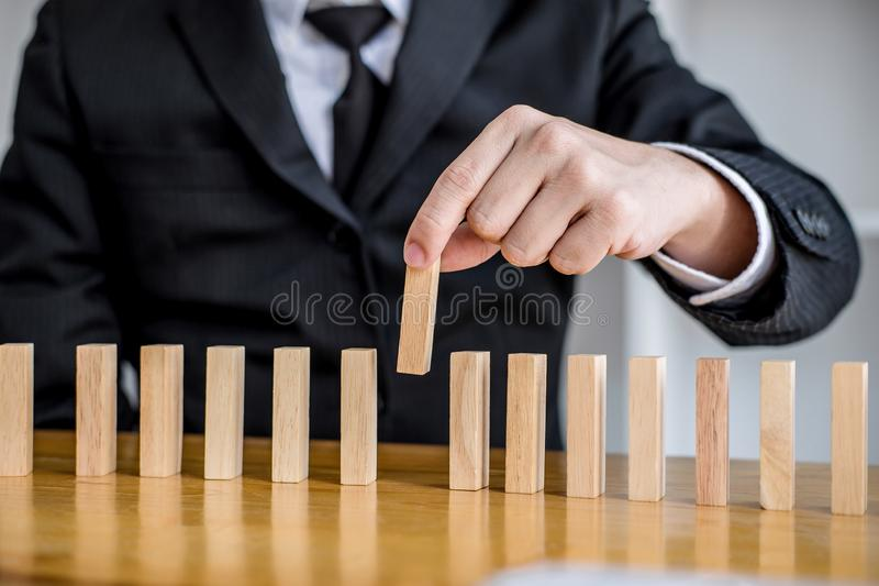 Wooden game strategy, Risk and strategy in business, Close up of businessman hand gambling placing wooden block on a line of. Domino royalty free stock photo