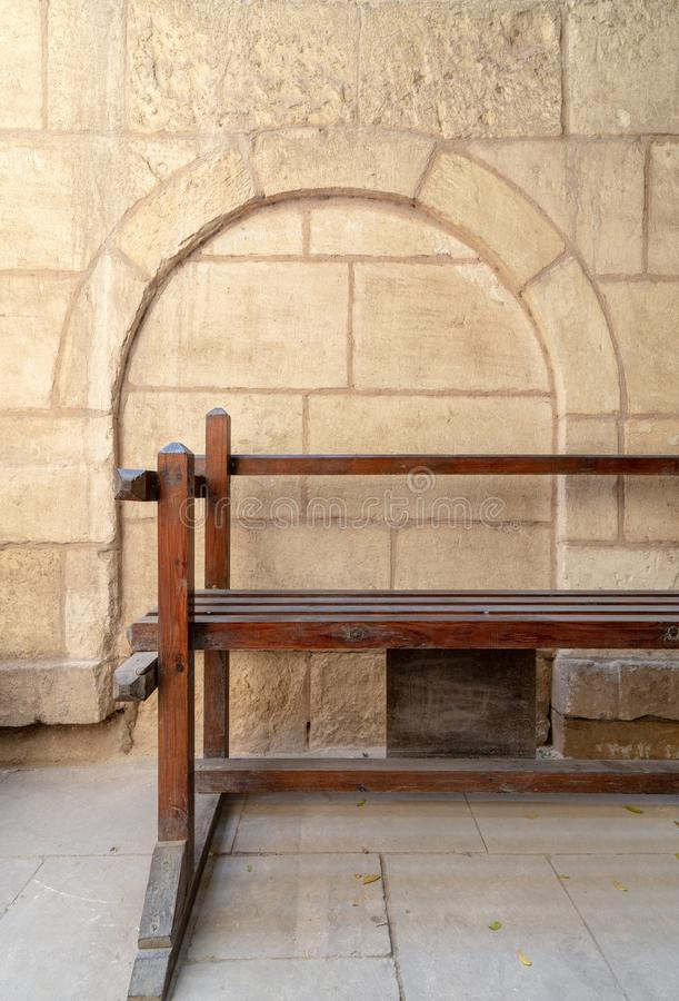 Wooden garden bench with background of stone bricks wall with arched niche at House of Egyptian Architecture, Cairo, Egypt. Wooden garden bench with background royalty free stock images