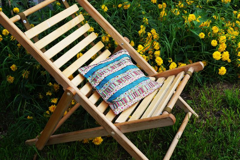 Wooden garden chair and home-made pillow of lonely fabric stock images