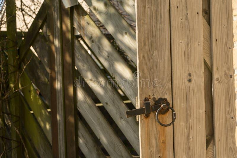 Wooden garden gate handle open gate. Metal rusty handle on open wooden door. Brown stock photo
