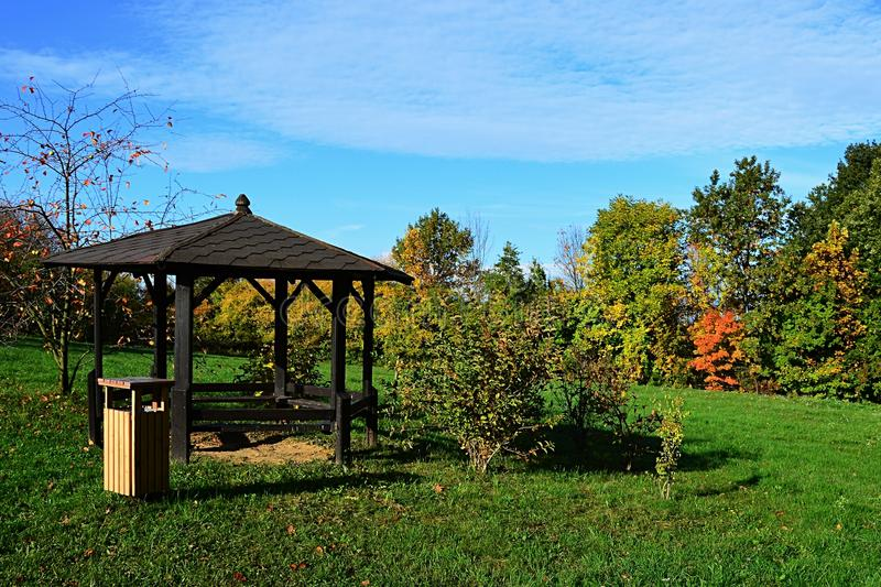 Wooden garden pergola or summer house with trash can on cultivated lawn during autumn season. Afternoon sunshine stock photography