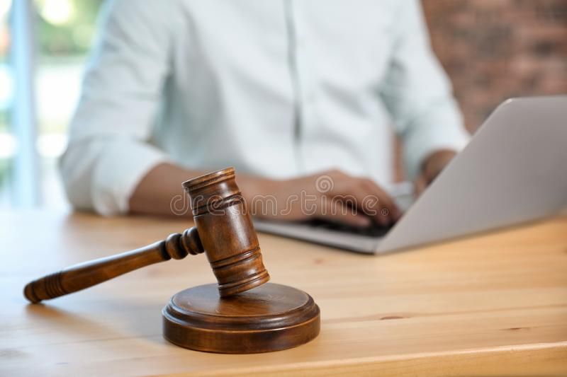 Wooden gavel and blurred notary with laptop. On background stock images