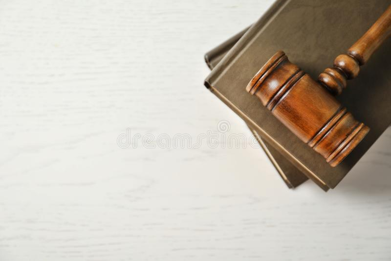 Wooden gavel and books on light table, top view. Law concept royalty free stock photo