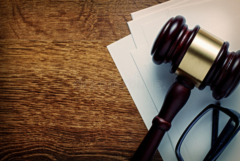Wooden gavel and glasses on notepaper. Wooden gavel with a brass band and glasses on notepaper conceptual of a judgement in law, justice or an auctioneers gavel stock image