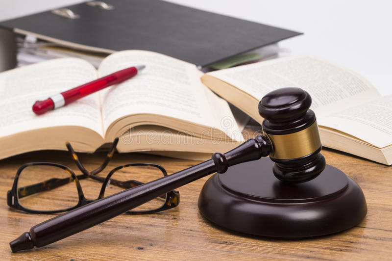 Wooden gavel on a table. Wooden judge gavel and books on a wooden table royalty free stock image