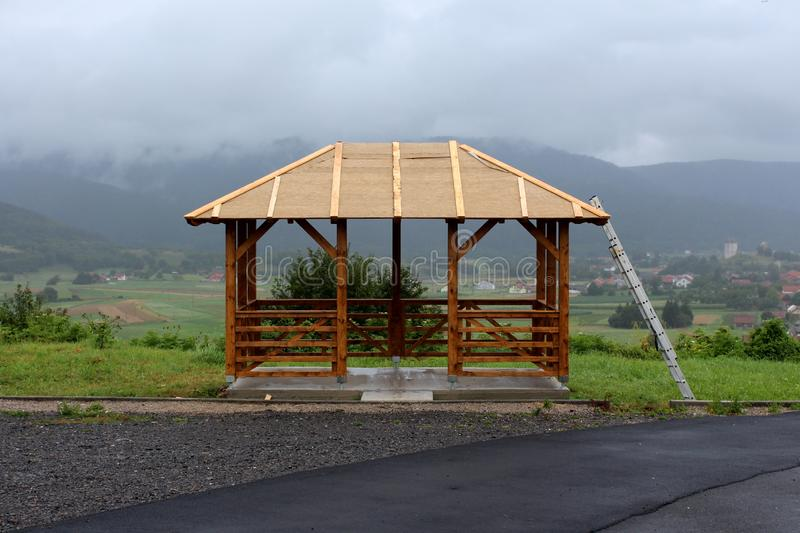 Wooden gazebo mounted on concrete foundation with roof still under construction overlooking small town and mountains in distance royalty free stock images
