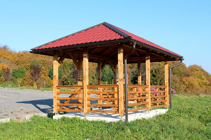 Wooden gazebo structure with new roof and gutter mounted on concrete foundation next to grass and gravel parking with dense trees stock photos