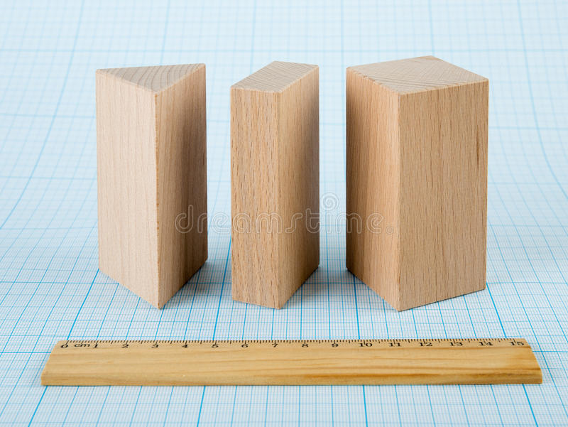 Wooden geometric shapes. On graph paper stock image