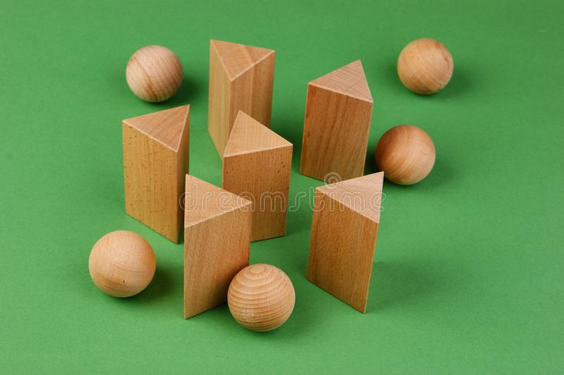 Wooden geometric shapes. On a green background royalty free stock photos