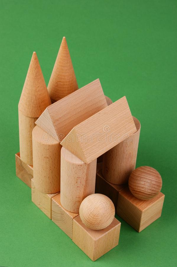 Wooden geometric shapes. On a green background stock photo