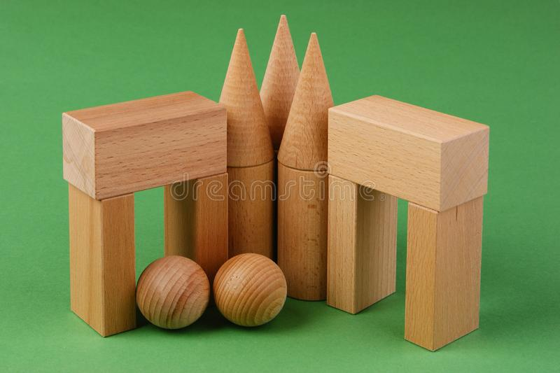 Wooden geometric shapes. On a green background royalty free stock images