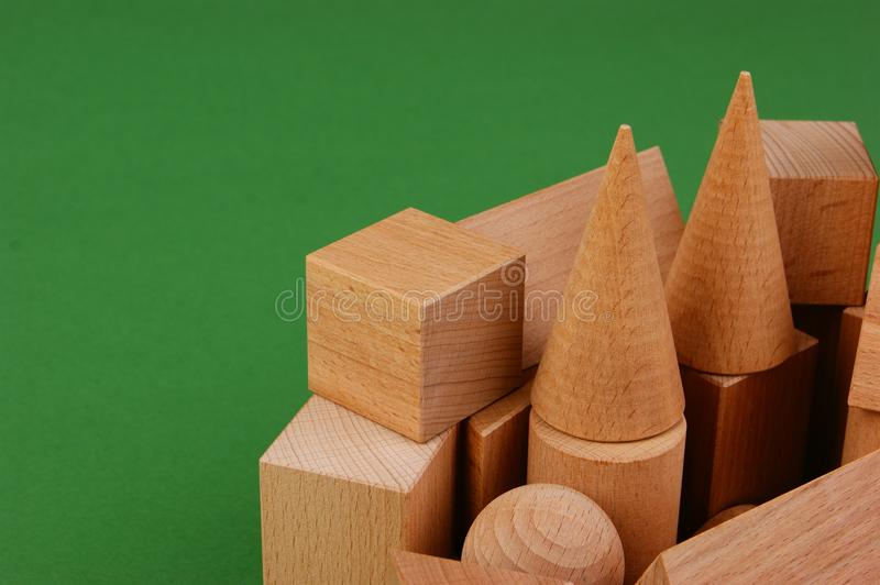 Wooden geometric shapes. On a green background royalty free stock photography