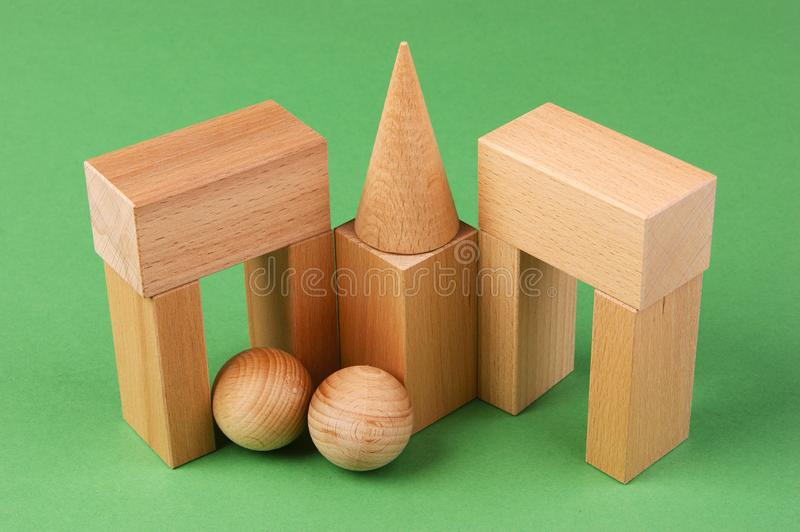 Wooden geometric shapes. On a green background royalty free stock image
