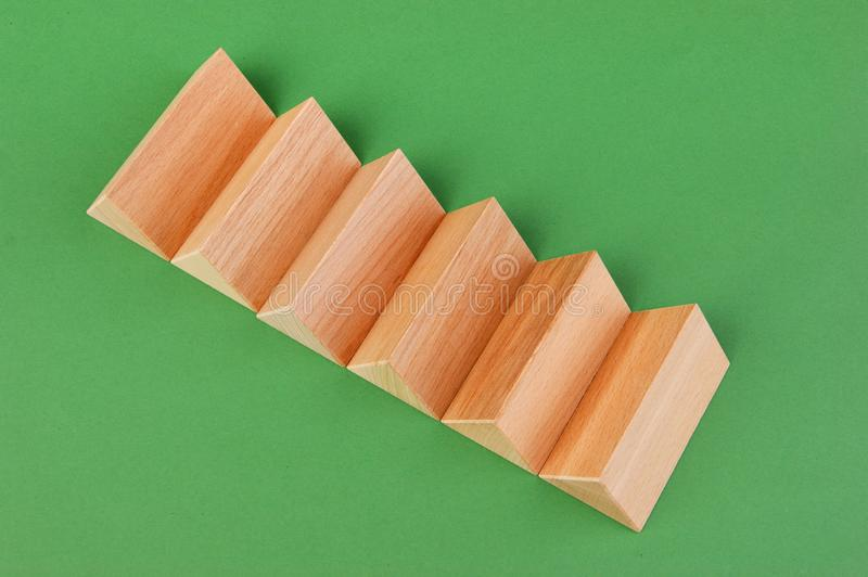 Wooden geometric shapes. On a green background royalty free stock photo