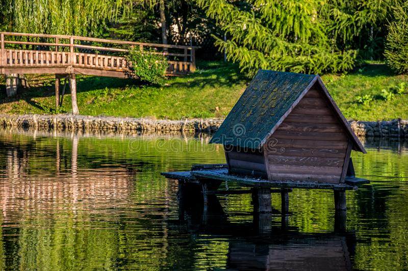 Wooden goose house on the lake stock photos