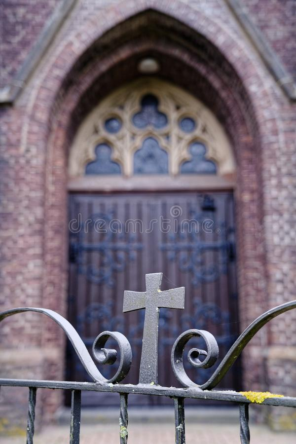 Wooden gothic church door behind an iron gate with cross royalty free stock photos
