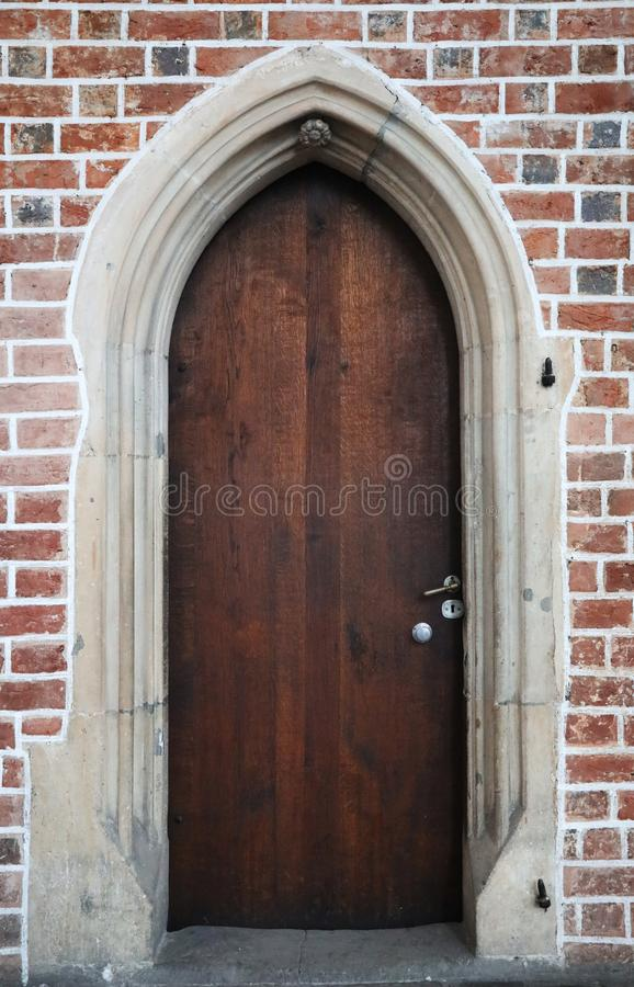 Wooden gothic doors in a brick wall stock image