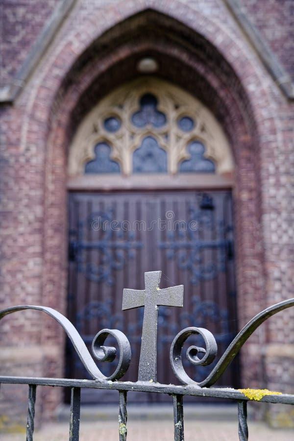 Wooden gothische kerkdeur achter een ijzeren poort met kruis royalty-vrije stock foto's