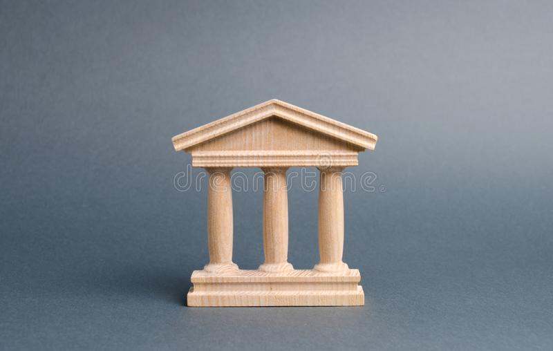 Wooden government building on a gray background. The authorities, the sovereignty of the country and the rule of law. concept. Of state administration and stock photos