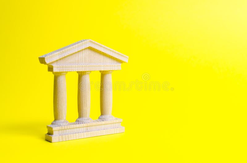 Wooden government building on a yellow background. The authorities, the sovereignty of the country and the rule of law. Concept of state administration and stock photos