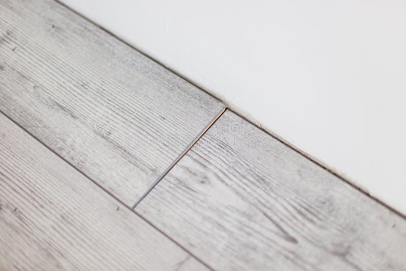 Wooden gray panels on new laminated flooring install on knock. Wooden gray panels on new laminated flooring stock photos