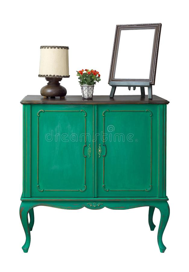 Wooden green vintage sideboard with empty desktop photo frame, flower planter, and table lamp isolated on white with clipping path royalty free stock photos