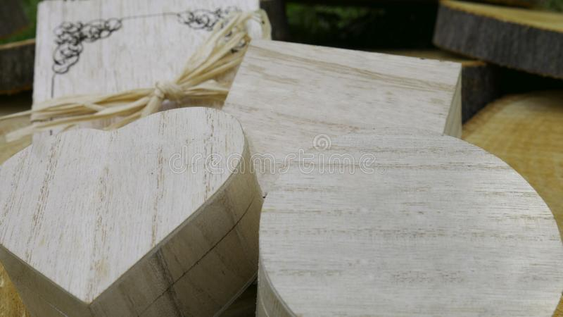 Wooden greeting card and a closed gift boxes of different shapes on wooden stump.  stock photo