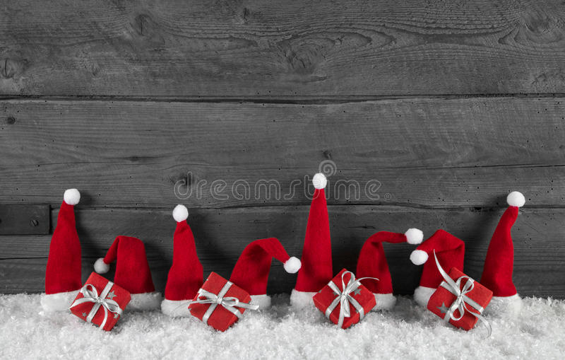 Wooden grey christmas background with red santa hats and gifts. Wooden grey christmas background with red santa hats and presents royalty free stock photo