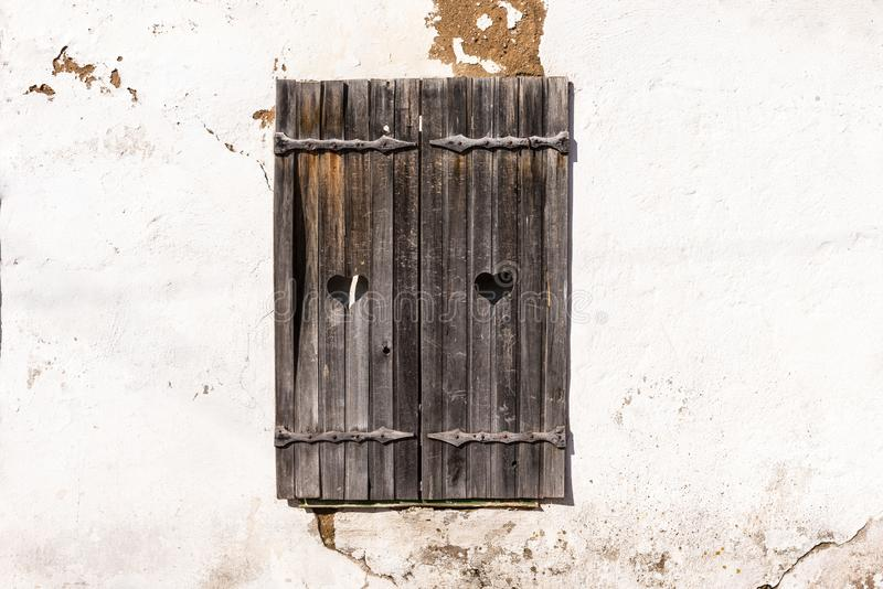 Wooden grey shutters with heart on old wall. Old wooden windows frame on stone wall stock photos