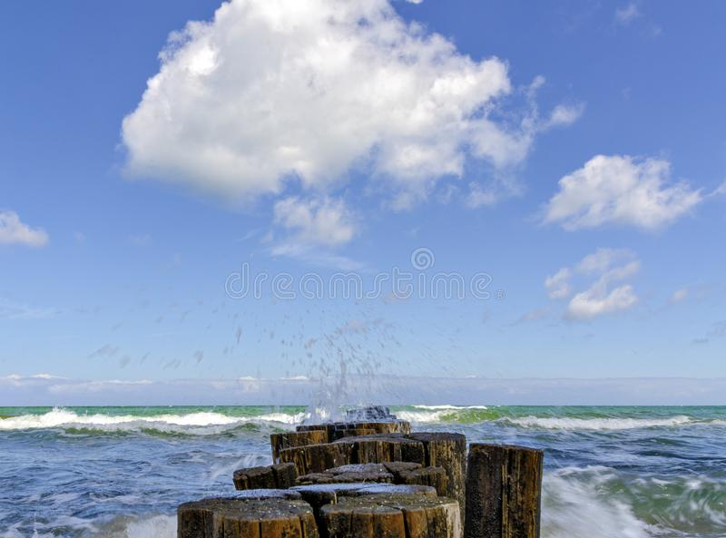 Wooden groin and wavy sea stock images