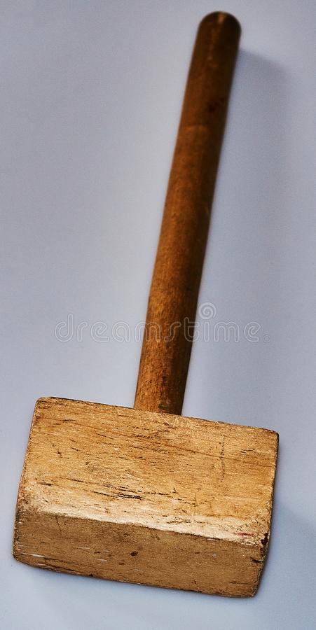 Wooden hammer on an background. A hammer from a tree lies on an background. The hammer was used in the work. There are traces of blows. An object, a beater, an stock photo