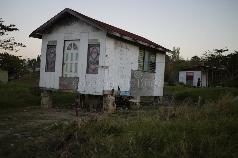 Wooden hand build house on bricks. Jamaican house cheaply made out of scrap wood balanced on bricks, a poor person lives here royalty free stock image