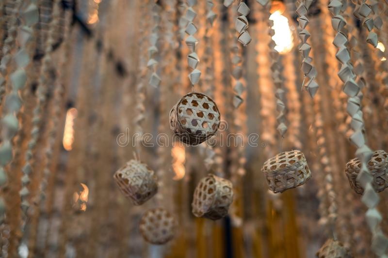 Wooden hand-crafted hanging decoration. The decoration is made of Bamboo stripes that hand weaved into a cylindrical shapes. Such decoration is commonly found royalty free stock photos