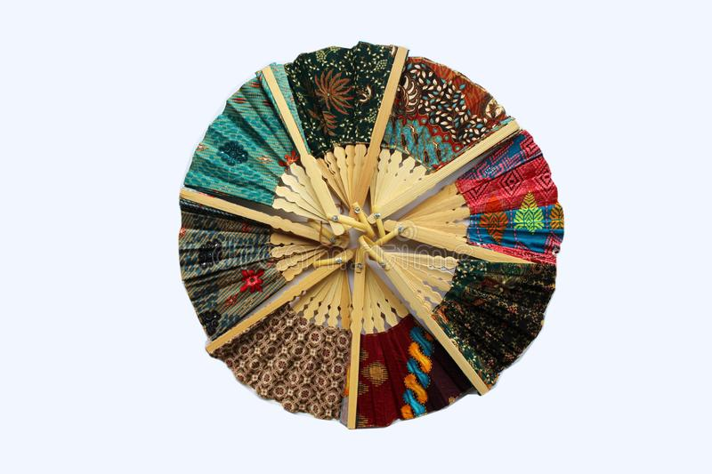 A wooden hand fan in Javanese cloth called batik stock photos
