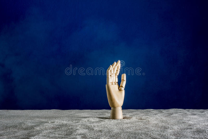Wooden hand gesticulating against a blue background. Gesticulation with a wooden hand sticking out of sand stock photo
