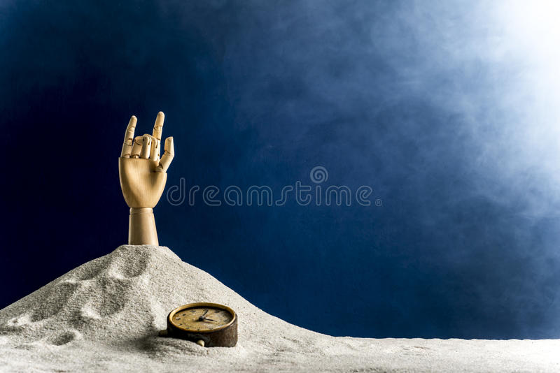 Wooden hand gesticulating against a blue background. Gesticulation with a wooden hand sticking out of sand royalty free stock photos