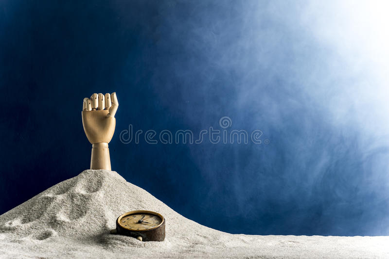 Wooden hand gesticulating against a blue background. Gesticulation with a wooden hand sticking out of sand royalty free stock images