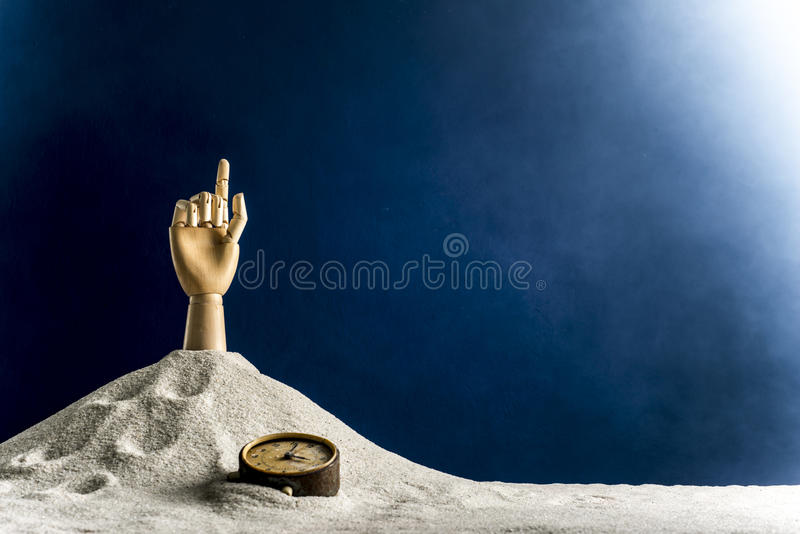 Wooden hand gesticulating against a blue background. Gesticulation with a wooden hand sticking out of sand stock image