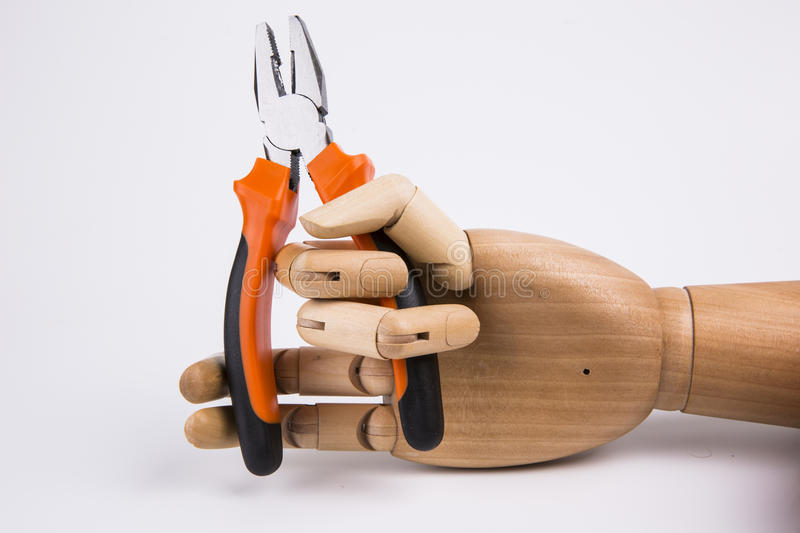 Wooden hand holding Pliers stock image