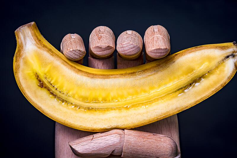Wooden hand holding a split banana in half. Wooden hand holding a banana split in half with black background stock images
