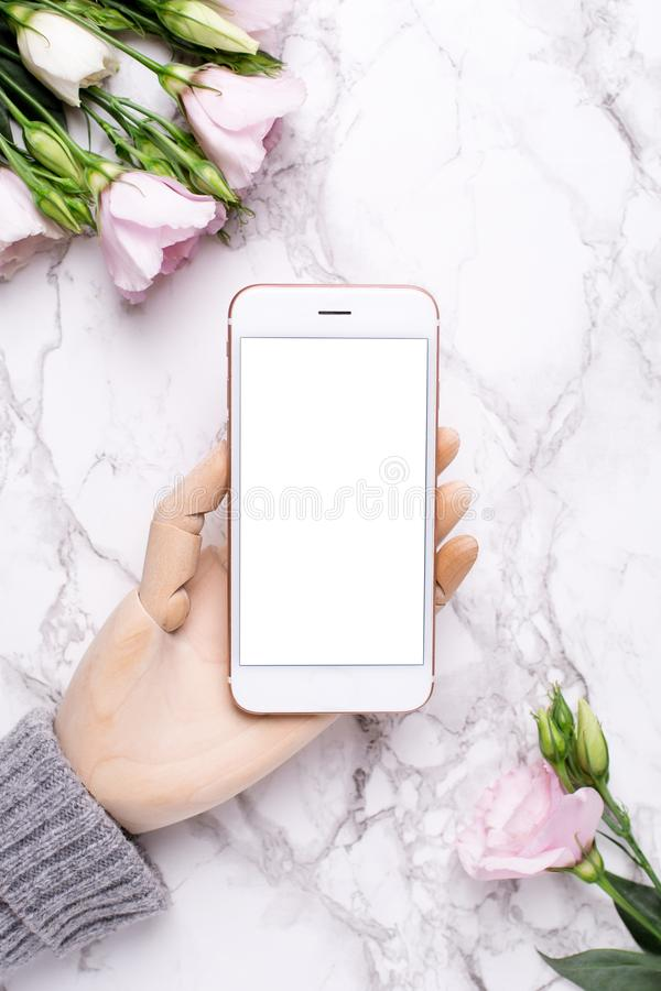 Wooden hand with mobile phone on marble office background with pink flowers royalty free stock photos