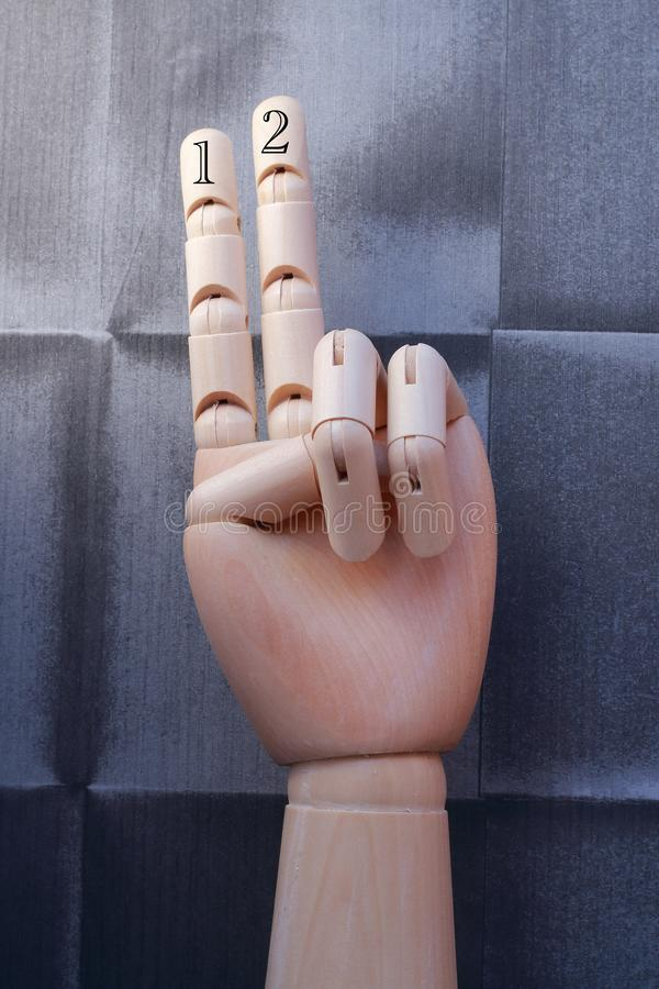 Wooden hand with two fingers raised and numbered with numbers one and two royalty free stock photo