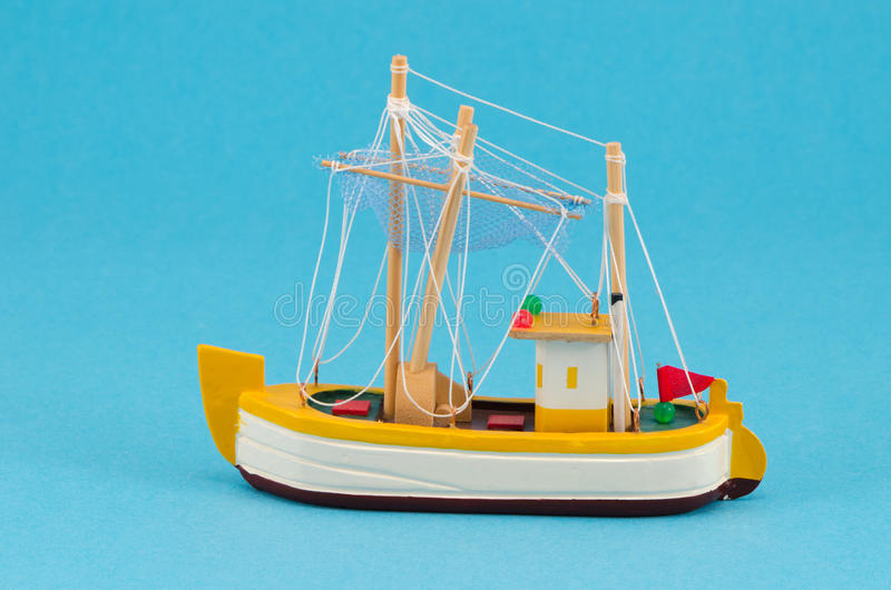 Wooden handmade boat ship model on blue background stock photo
