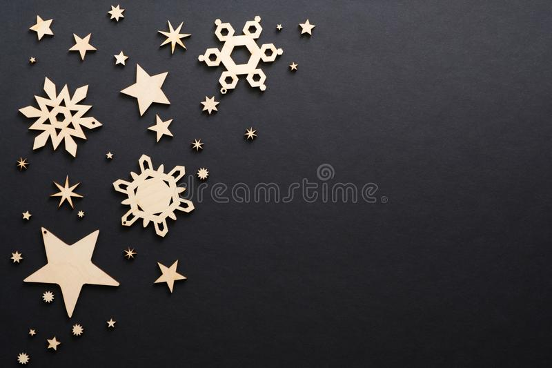 Wooden handmade Christmas decorations on dark black background. Christmas snowflakes and stars with copy space. Flat lay, top view stock photos