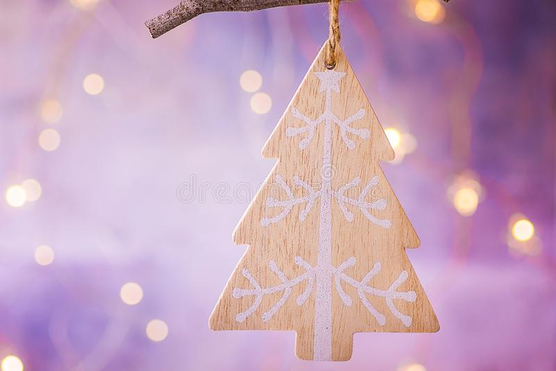 Wooden handmade Christmas tree ornament hanging on branch. Shining garland golden lights. Purple background. Magical atmosphere. Copy space. Greeting card royalty free stock image