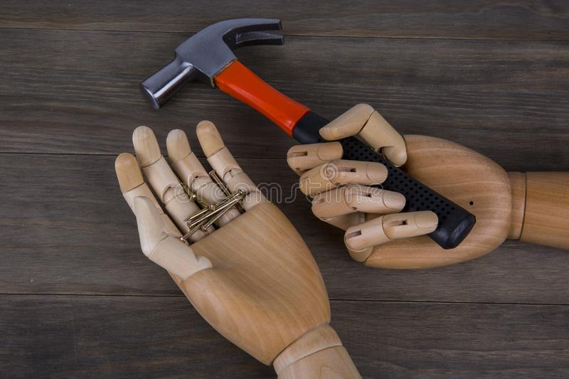 Wooden hands holding hammers and nails stock photography