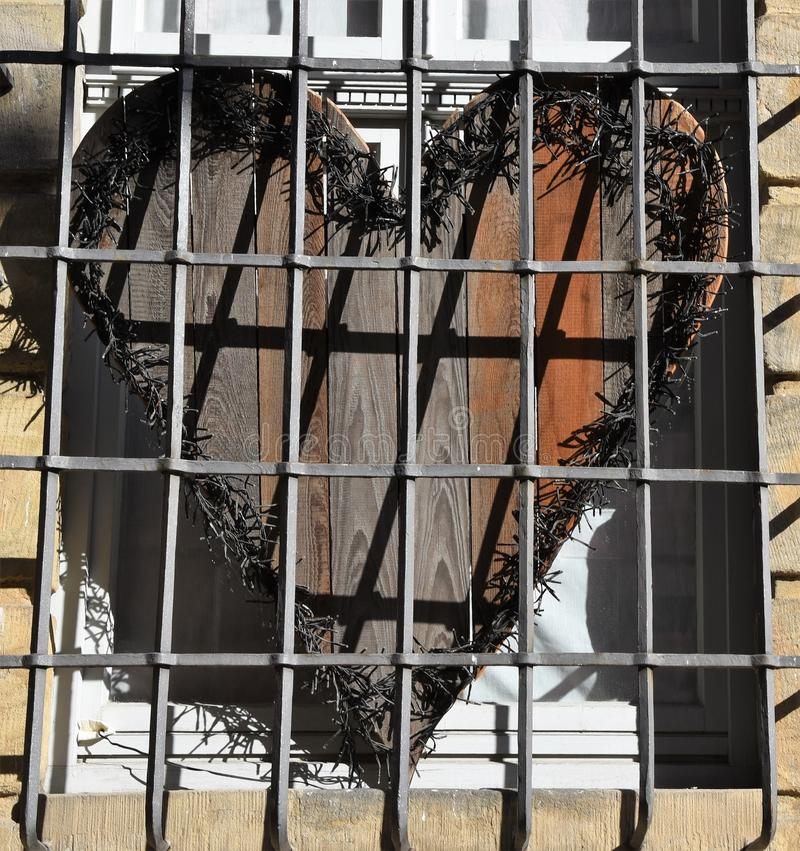 A wooden heart behind bars. Is used as a window decoration representing that sometimes love can be our prison stock image