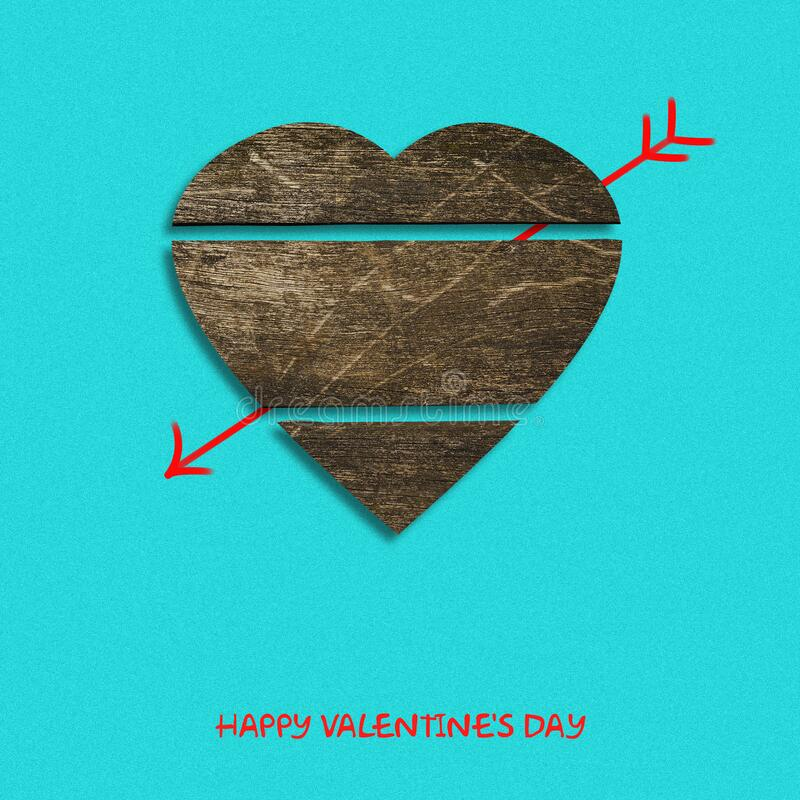 Wooden heart and cupid`s arrow on a pastel green background. Happy valentines day background. royalty free stock images