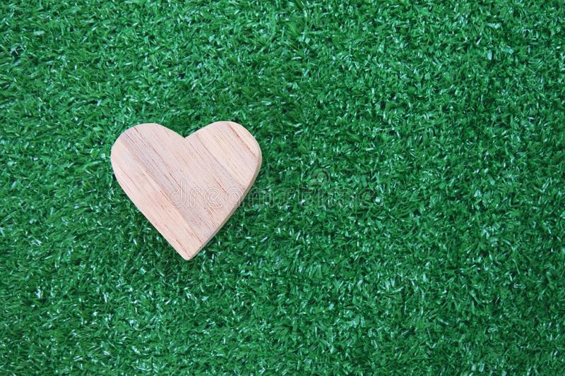 Wooden heart model on artificial green grass. Love concept. Copy space. Wooden heart model on artificial green grass. Love concept. Copy space royalty free stock image